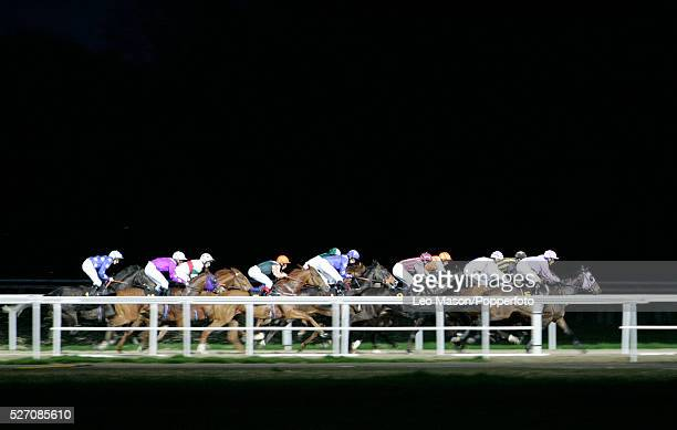 of an evening race meeting in the dark at Kempton Park race course in London England UK