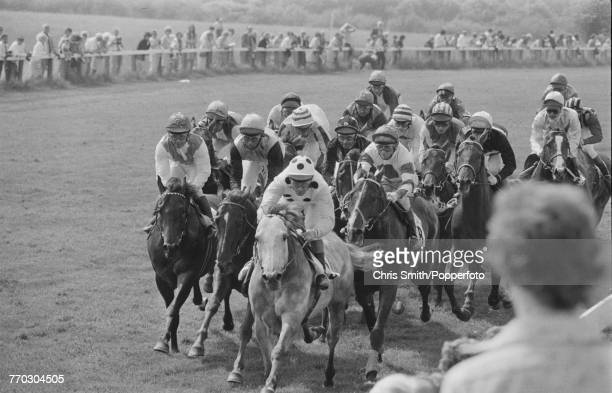 View of horses and riders racing around Tattenham Corner with Grey Thunder leading as they compete in the 1974 Epsom Derby at Epsom Downs Racecourse...