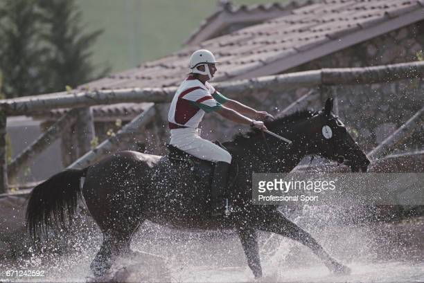 View of Hungarian equestrian Attila Soos riding Zsizsik negotiating a water hazard during competition to finish in 31st place in the Mixed ThreeDay...