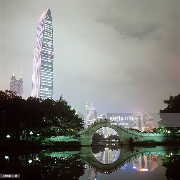 View of illuminated city buildings across water at night, Shenzhen, China