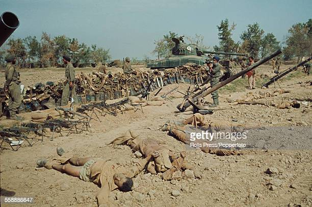 View of Indian soldiers on patrol either side of a Sherman tank observing corpses of dead soldiers along with a cache of arms and military equipment...