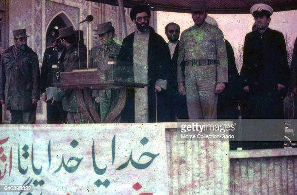 View of Iranian President Ali Khamenei surrounded by soldiers and clerics speaking on stage at a lectern in Iran March 1983 The banner attached to...
