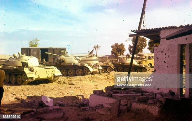 View of Israeli military tanks and vehicles idling in the dirt outside of a destroyed building in Gaza Israel November 1967