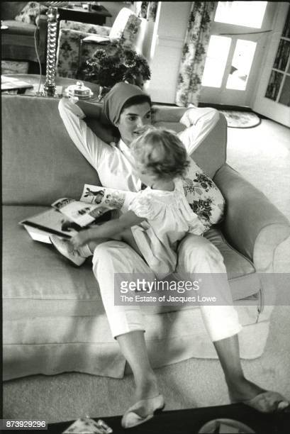 View of Jacqueline Kennedy as she relaxes on a sofa her daughter Caroline on her lap Hyannis Port Massachusetts August 1960
