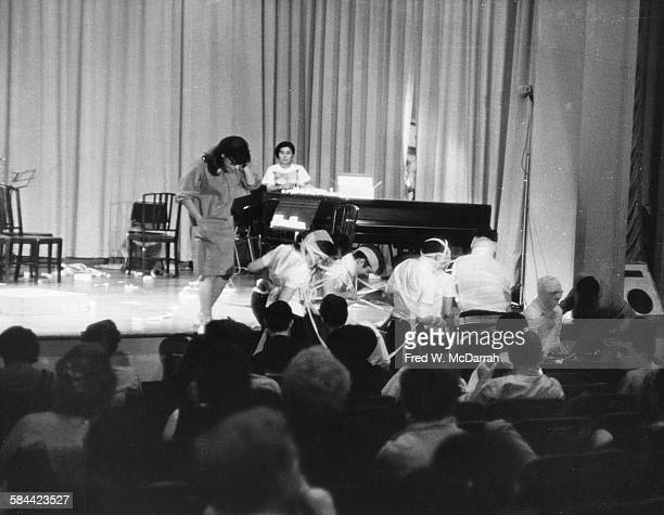 View of Japaneseborn American artist and musician Yoko Ono and musicians wrapped in ribbon during a performance at a Fluxus event New York New York...
