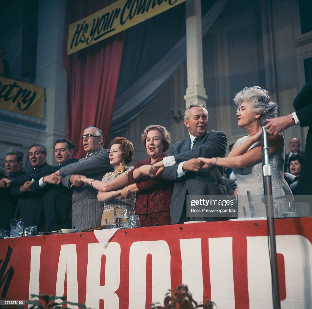 View of Labour Party politicians standing together and linking hands on the platform as they sing 'The Red Flag', the traditional song to end the Labour Party annual conference in Scarborough, England in October 1967. From left to right are Tony Benn, James Callaghan, unidentified, Richard Crossman, Barbara Castle, Alice Bacon, Prime Minister Harold Wilson and Jennie Lee.