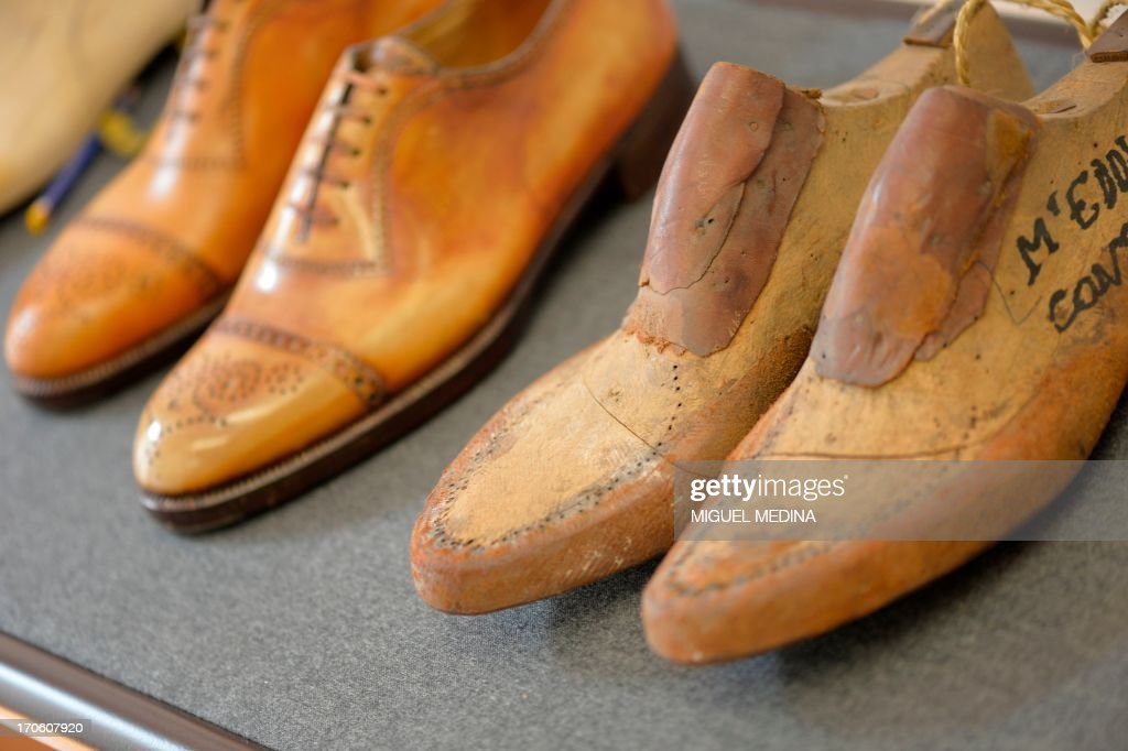 View of leather shoes displayed next to a mold in the workshop of luxury brand Berluti in Paris on June 15, 2013. Berluti operates as made-to-measure footwear, in particular mens boots and ready-to-wear.
