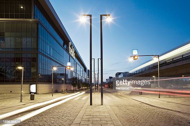 View of light trails on street on modern city at dusk