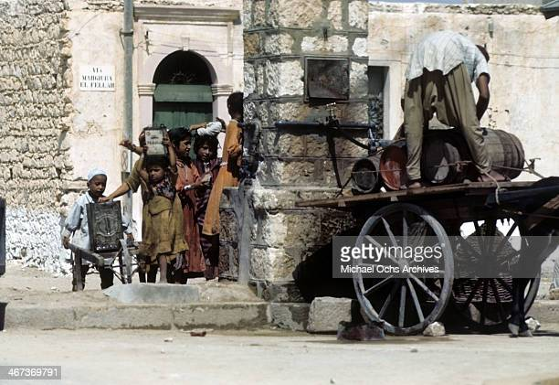 A view of local Libyanese children wearing native clothes carry supplies in the street in Benghazi Libya