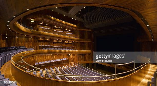 View of main auditorium showing 'horseshoe' of seating with orchestra pit open fully open black American walnut finishings and purple l Wexford Opera...