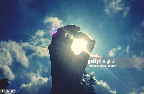 View of man holding hand to sun