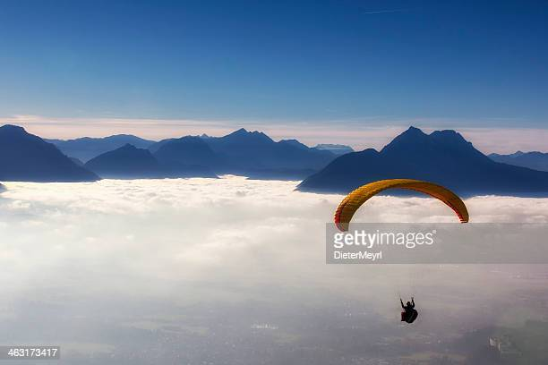 View of man skydiving from above the clouds with mountains