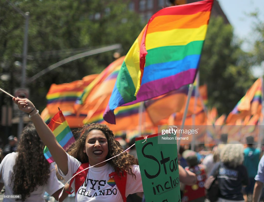A view of marchers with a rainbow flag and signs in trbute to Orlando during the New York City Pride 2016 march on June 26, 2016 in New York City.