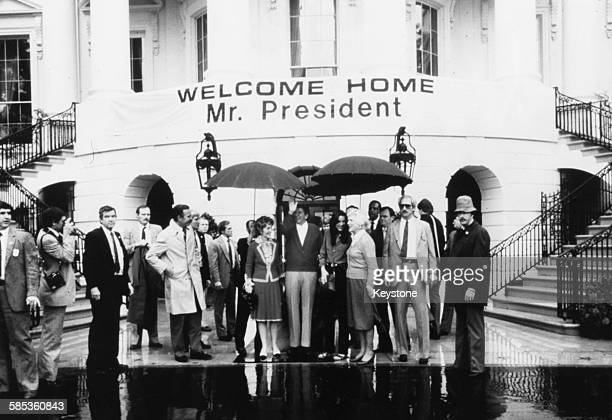 President Ronald Reagan waving to the crowd under a 'welcome home Mr President' sign surrounded by his family and bodyguards as he returns to the...
