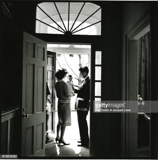 View of married couple Jacqueline Kennedy and Senator John F Kennedy as the latter says goodbye to their daughter Caroline in the doorway of their...