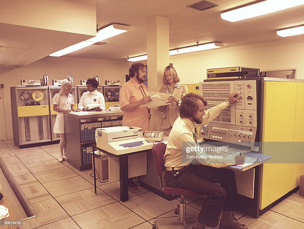 View of medical workers and nurses in a computer room with early IBM computer, 1980.