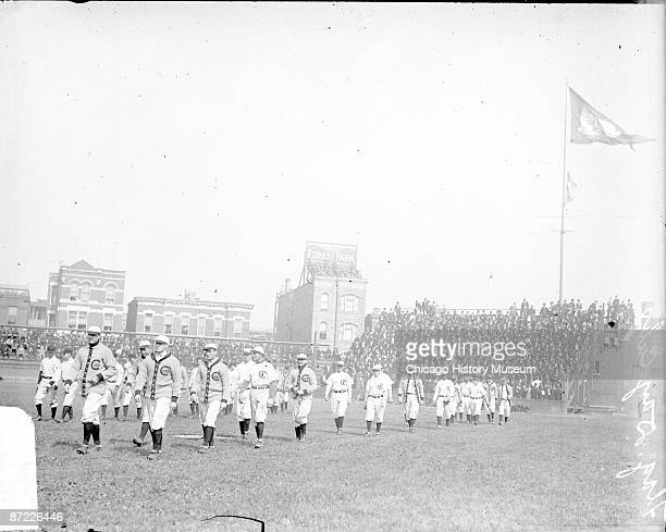 View of members of National League's Chicago Cubs baseball team walking on the field during a pennantraising ceremony at West Side Grounds located...