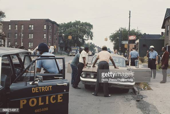View of members of the Detroit Police Department stopping and searching suspects on a street in Detroit during a period of rioting and unrest...