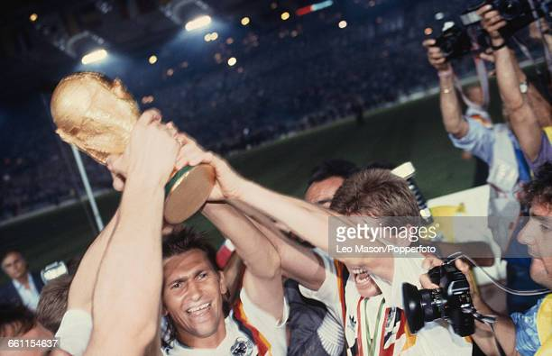 View of members of the West Germany football team including Klaus Augenthaler on left and Andreas Moeller on right pictured lifting up the FIFA World...