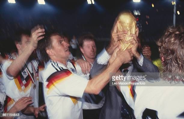 View of members of the West Germany football team surround Klaus Augenthaler as he lifts up the FIFA World Cup Trophy after winning the final of the...