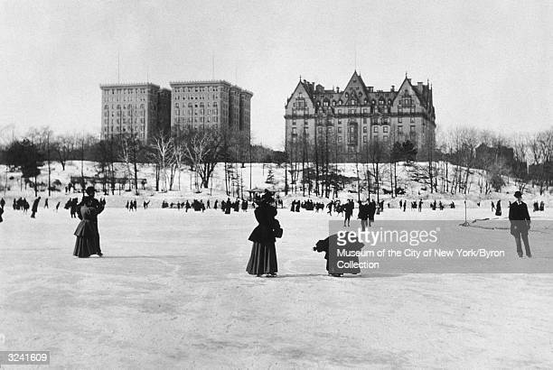 View of men and women ice skating on a frozen pond in Central Park New York City looking towards the Hotel Majestic and the Dakota apartment...