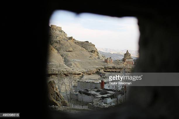 A view of mudbrick homes stupas and ruins can be seen through the windows of Pema Dolma's cliffside home on May 23 2014 in Chosher Nepal Humans have...