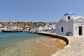 View of Mykonos typical chapel next to Mykonos harbor and the Aegean sea, with white village in the background.