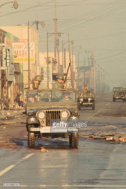 View of National Guardsmen in Jeeps as they patrol the streets of the Watts neighborhood during riots Los Angeles California July 1965