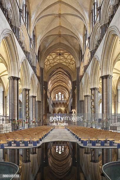 View of Nave and Christmas nativity scene in Salisbury Cathedral with the ceiling reflected in water in the font