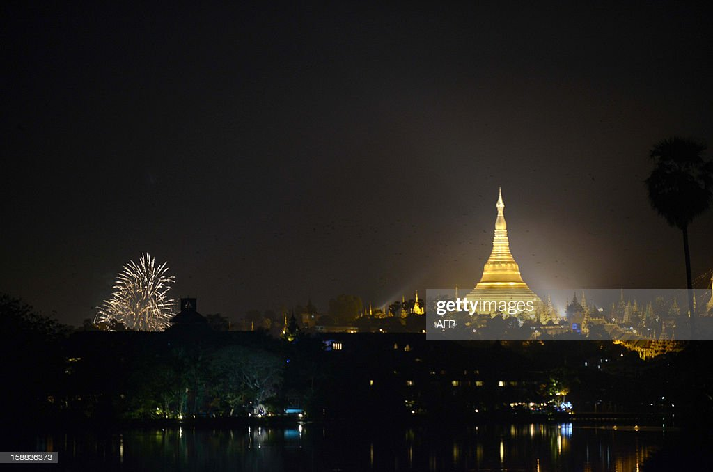A view of New Year fireworks near the Shwe Da Gon pagoda at Kandawgyi Lake in Yangon on December 31, 2012. Some 50,000 people were expected to gather at the revered golden Shwedagon Pagoda in Yangon for the city's first public countdown to the New Year and fireworks. AFP PHOTO / Ye Aung Thu