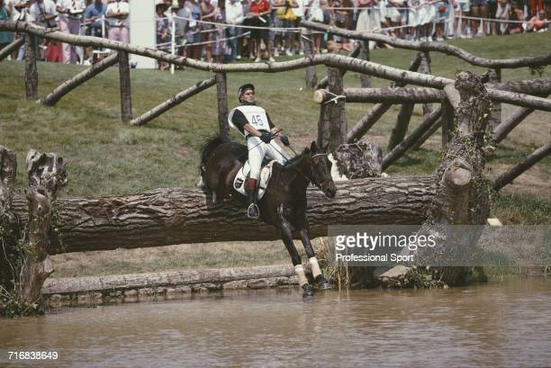 View of New Zealand equestrian Blyth Tait competitor riding Messiah negotiating a wooden log hazard in to water during competition in the cross...