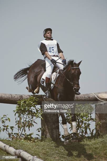 View of New Zealand equestrian Blyth Tait riding Messiah negotiating a wooden hazard and grass slope during competition in the cross country section...