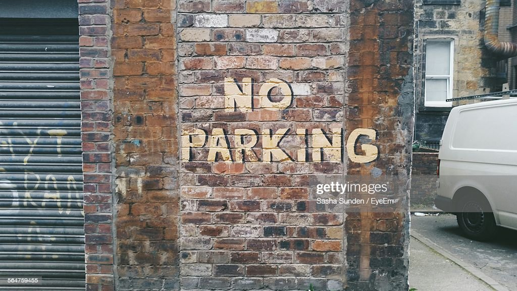 View Of No Parking Text On Brick Wall