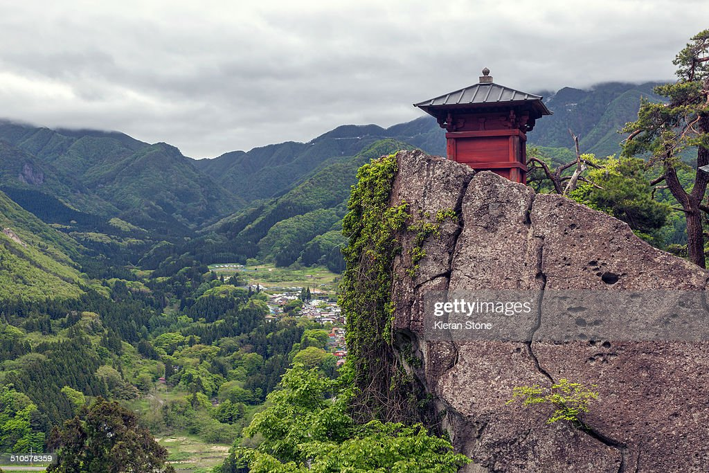 View of Nokyodo building on top of a cliff on the mountainside with views of the town in the valley below Yamagata Japan