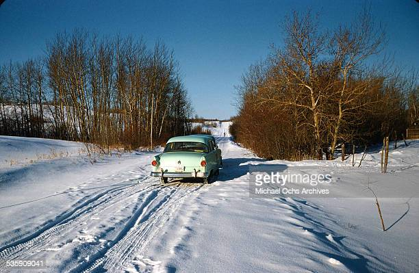 A view of North Dakota scenery of a car driving down a snowy road