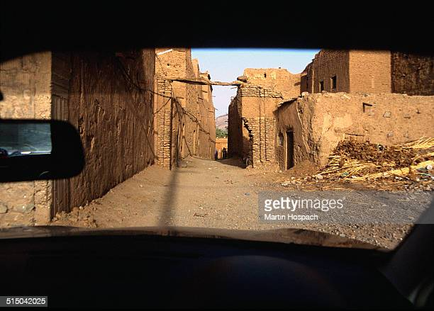 View of old ruin buildings through windshield, Agdz, Morocco