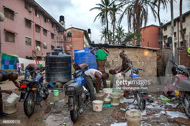 A view of one of the many neighborhood public spaces that have been converted into a motorcycle washing station against the master plan of the Festac...