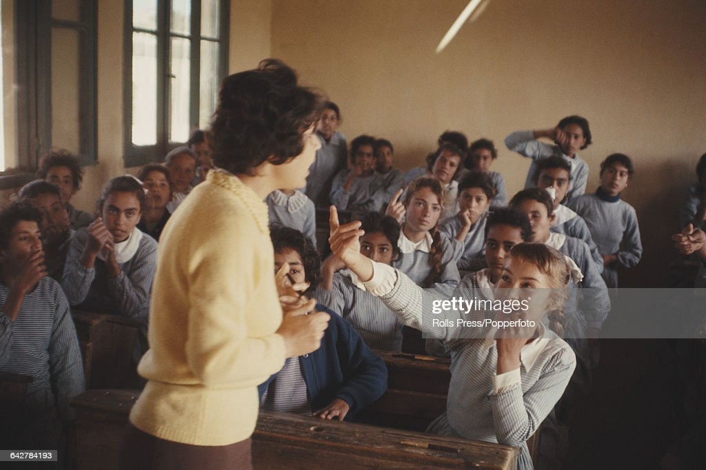 View of Palestinian children sitting at desks in a classroom being taught by a female teacher in a classroom of a school inside the Jabalia refugee...