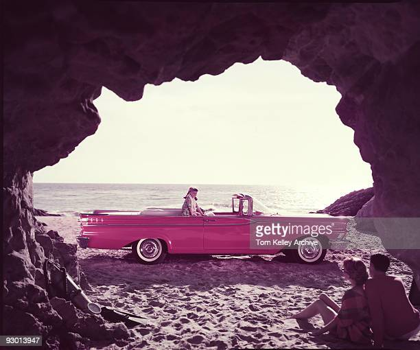 View of parents sitting inside a beach cave while watching their daughter who sits on their red Mercury Monterey convertible 1959