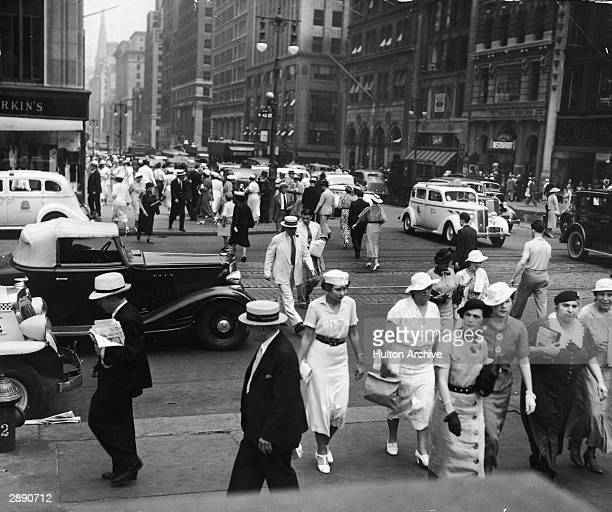 View of pedestrian and vehicle traffic at the intersection of 42nd Street and 5th Avenue New York New York circa 1930 The spire of St Patrick's...