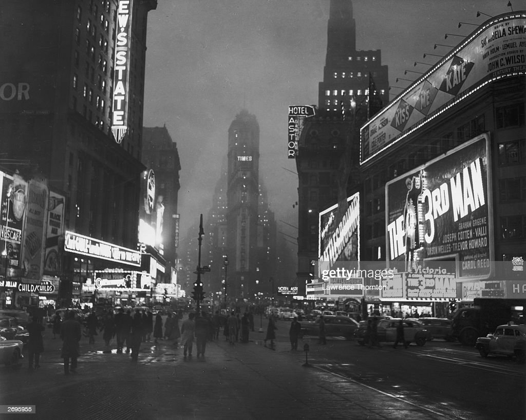 View of pedestrians and cars moving between theaters storefronts and hotels lit up with neon signs at night along Broadway in Times Square New York...