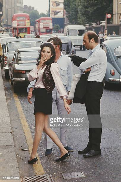 View of pedestrians including a young woman wearing a mini skirt standing on and beside the Kings Road in Chelsea London during the summer of 1967