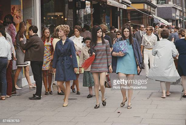 View of pedestrians including two young girls wearing mini dresses walking past shops during a busy shopping day on the Kings Road in Chelsea London...