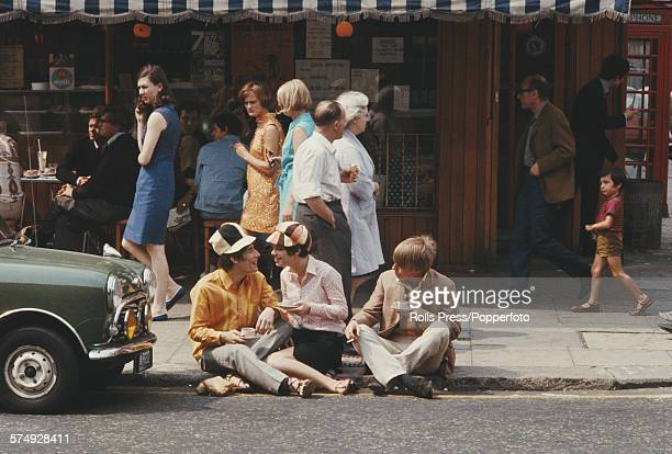 View of pedestrians passing three young people sitting on a kerb drinking cups of coffee outside a coffee shop on the Kings Road in Chelsea London...