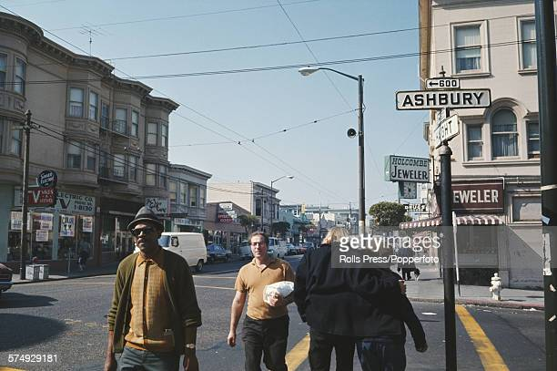View of pedestrians walking along a sidewalk by the intersection of Haight and Ashbury streets in the HaightAshbury district of San Francisco during...