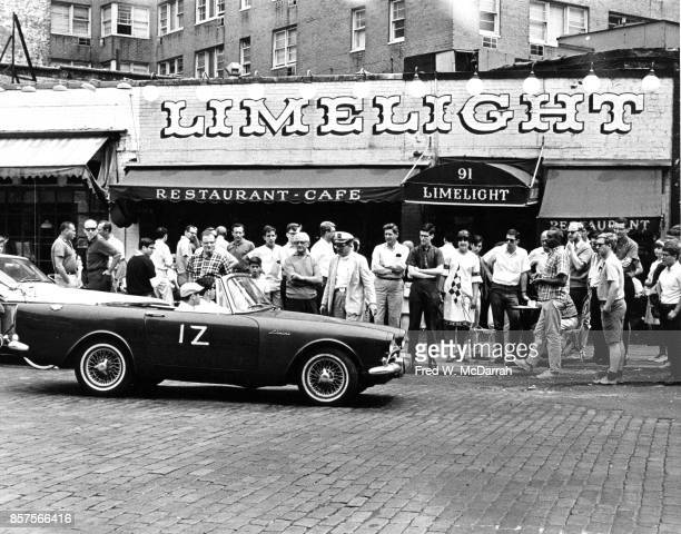 View of people gathered on the sidewalk in front of the Limelight Coffee House to watch the seventh annual Village Voice Auto Rallye New York New...