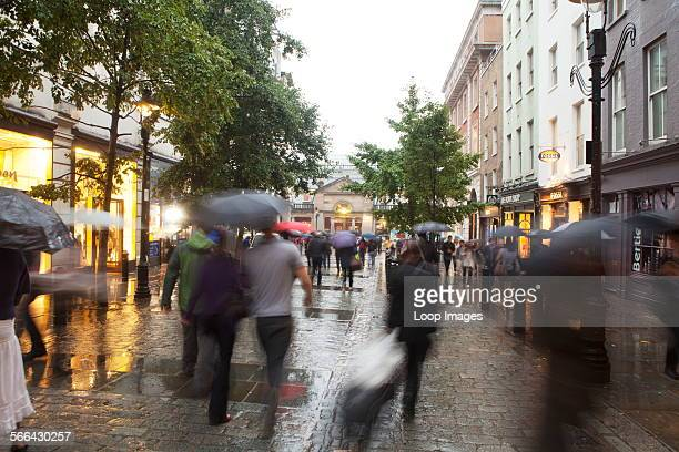 A view of people walking in the rain around Covent Garden