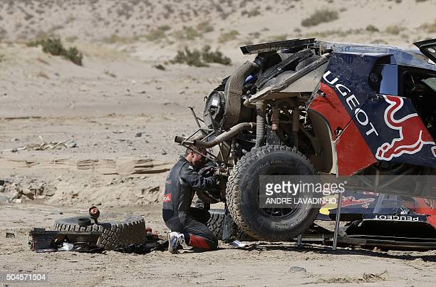 View of Peugeot French driver Sebastien Loeb and codriver Daniel Elena's overturned car after it was put back on its wheels during Stage 8 of the...