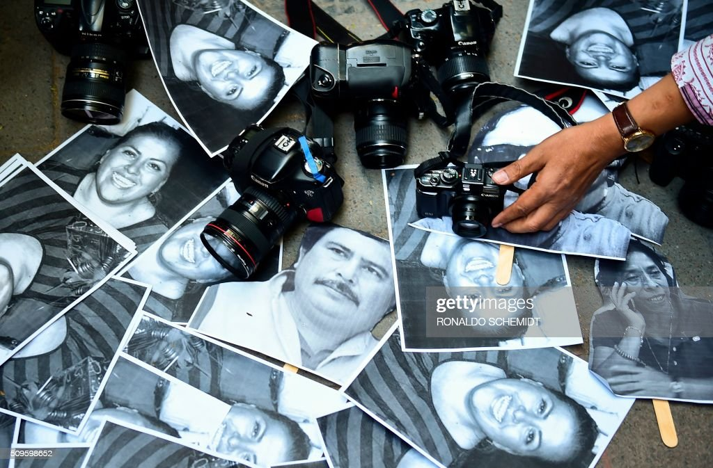 View of photos of killed journalists and cameras outside the Veracruz state representation office during a journalists protest in Mexico City on February 11, 2016. Mexican journalist Anabel Flores Salazar's funeral took place Wednesday after she was found killed at a road after being kidnapped Monday in Veracruz state, one of the most dangerous for journalists. AFP PHOTO/RONALDO SCHEMIDT / AFP / RONALDO SCHEMIDT
