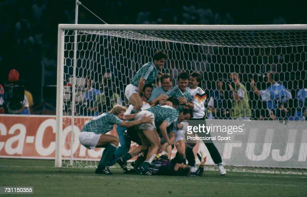 View of players from the West Germany team celebrating with goalkeeper Bodo Illgner after they beat England in the penalty shoot out to win the semi...